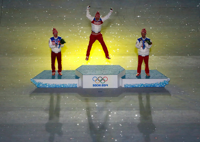 Gold medalist Alexander Legkov jumps on the podium beside silver medalist Maxim Vylegzhanin (L) and bronze medalist Ilia Chernousov (R), all of Russia, after they were presented with their medals in the men's cross-country 50 km mass start free event during the closing ceremony for the 2014 Sochi Winter Olympics, February 23, 2014. (Reuters / Eric Gaillard)