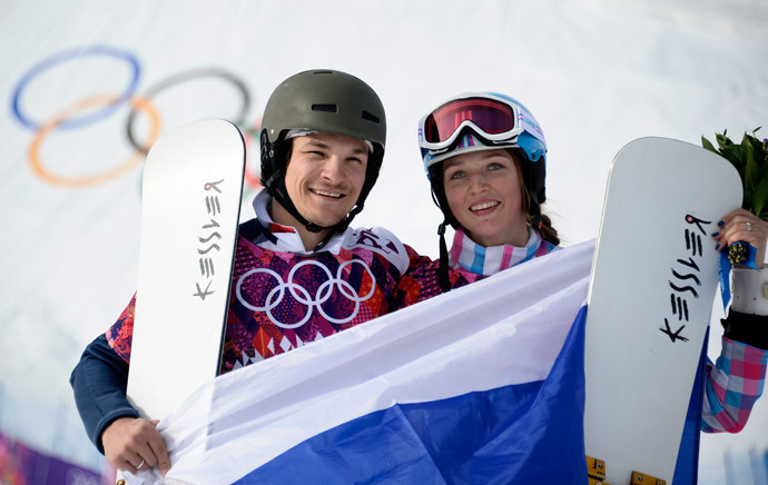 Gold Medallist, Russia's Vic Wild, and his wife, Bronze Medallist Alena Zavarzina, celebrate at the Snowboard Parallel Giant Slalom Flower Ceremony at the Rosa Khutor Extreme Park during the Sochi Winter Olympics on February 19, 2014. (AFP Photo / Franck Fife)