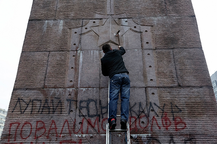 "An anti-Yanukovich protester attempts to demolish the ""Monument to Soviet secret security service (chekists) - fighters of the revolution"" in Kiev February 23, 2014 (Reuters / Konstantin Chernichkin)"