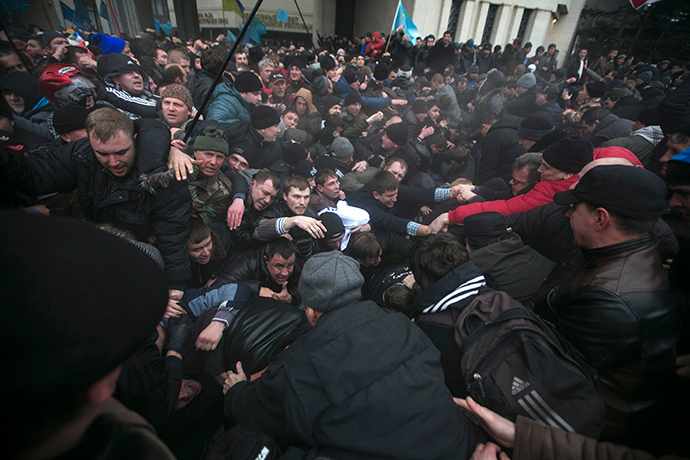 Ukrainian men help pull one another out of a stampede during clashes at rallies held by ethnic Russians and Crimean Tatars near the Crimean parliament building in Simferopol February 26, 2014 (Reuters / Baz Ratner)
