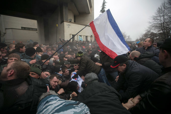 Ukrainian men help pull one another out of a stampede as a flag of Crimea is seen during clashes at rallies held by ethnic Russians and Crimean Tatars near the Crimean parliament building in Simferopol February 26, 2014. (Reuters / Baz Ratner)
