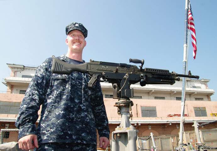 "A US naval officer displays an automatic weapon mounted on the USS Taylor in Odessa on July 14, 2010 during the US-Ukraine joint maritime exercises ""Sea Breeze 2010"". (AFP Photo / Alexey Kravtsov)"