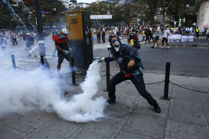 An anti-government demonstrator throws a teargas canister after it was thrown at protesters by the police, during clashes at Altamira square in Caracas February 27, 2014. (Reuters/Tomas Bravo)