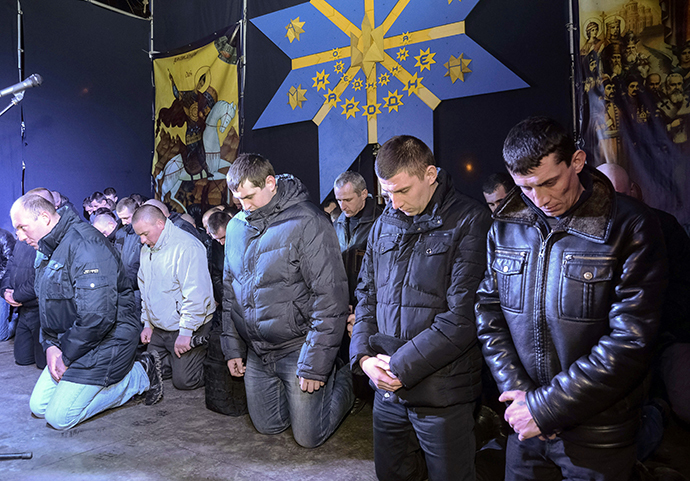 Local riot police kneel as they apologize to Lviv residents for taking part in an operation against anti-government protesters in Kiev but said that they did not beat protesters, during a rally in central Lviv February 24, 2014. (Reuters / Roman Baluk)