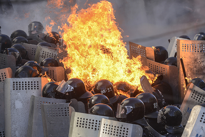 Interior Ministry members are on fire, caused by molotov cocktails hurled by anti-government protesters, as they stand guard during clashes in Kiev February 18, 2014. (Reuters / Andrew Kravchenko)