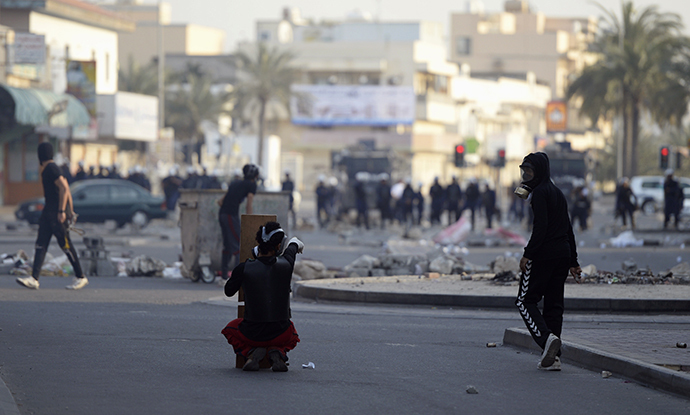 Protesters react towards riot police during clashes taking place during a protest over the death of detainee Jaffar Mohammed Jaffar at a hospital, ahead of his funeral in the village of Daih, west of Manama, February 27, 2014. (Reuters)