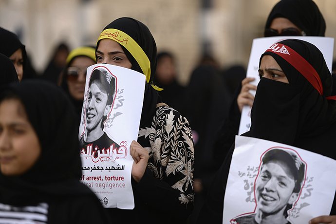 Protesters hold pictures of detainee Jaffar Mohammed Jaffar during a protest over his death at a hospital, ahead of his funeral in the village of Daih, west of Manama, February 27, 2014. (Reuters)