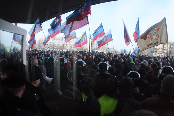 A line of police stand guard as pro-Russian protesters wave Russian flags during a rally in front of the regional administration building in the industrial Ukrainian city of Donetsk on March 1, 2014 (AFP Photo / Alexander Khudoteply)