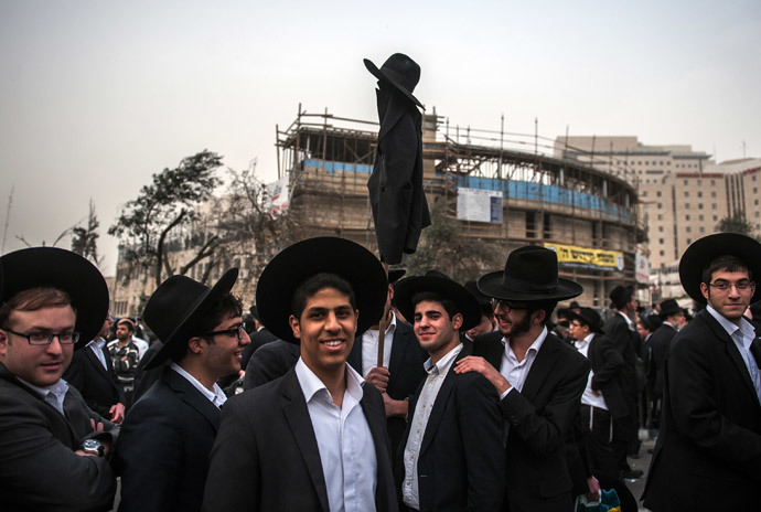 Ultra-Orthodox Jews hold a coat and a hat on a stick as they take part in a mass prayer vigil in Jerusalem on March 2, 2014 .(AFP Photo / David Buimovitch)