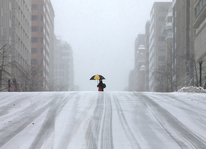 A man walks along a snow covered street, on March 3, 2014 in Washington, DC. (AFP Photo / Mark Wilson)