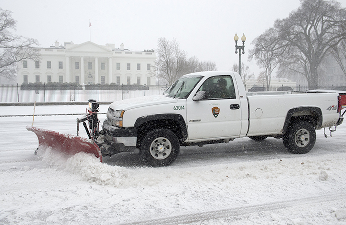 A snowplow moves snow from the street in front of the White House in Washington, DC, March 3, 2014, during a snow storm. (AFP Photo / Saul Loeb)