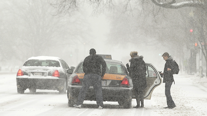 People get into a scarce taxicab during a blizzard in Washington March 3, 2014. (Reuters / Gary Cameron)
