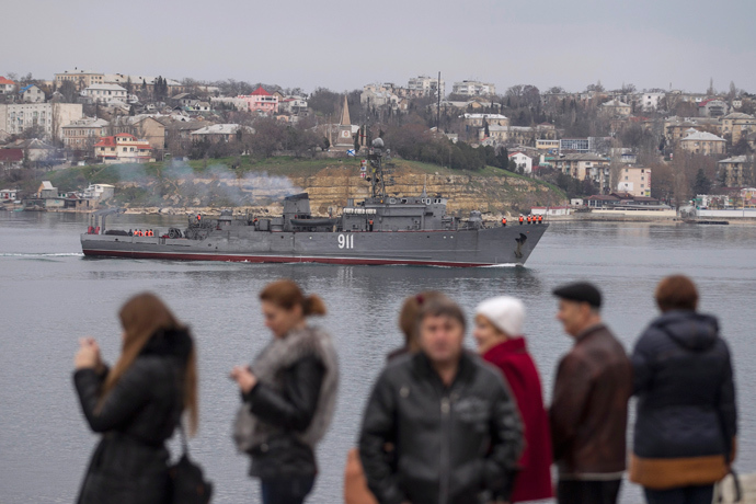 People watch a Russian Navy ship enter the Crimean port city of Sevastopol March 2, 2014 (Reuters / Baz Ratner)