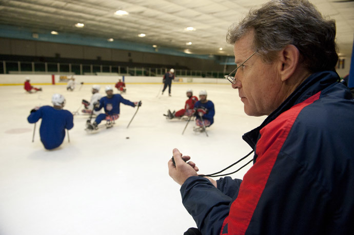 U.S. Paralympic Sled Hockey Team Athletic Trainer Mike Cortese watches his stop watch as the team practices speed drills during the team's last U.S. based practice at the Sertich Ice Arena in Colorado Springs, Colorado on February 27, 2014.(AFP Photo / Jason Connolly)