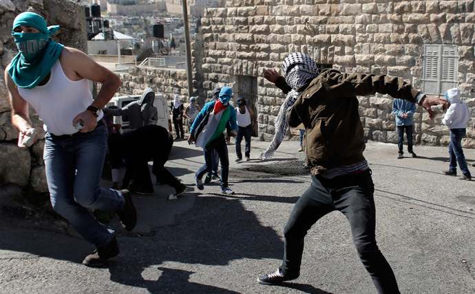 Palestinians throw stones toward Israeli police during clashes in East Jerusalem neighborhood of Ras al-Amud, following noon prayers, on February 28, 2014.(AFP Photo / Ahmad Gharabli)