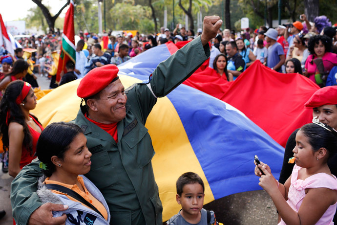 A man dressed as late Venezuelan President Hugo Chavez waves during the Carnival festival in Caracas March 4, 2014.(Reuters / Carlos Garcia Rawlins)