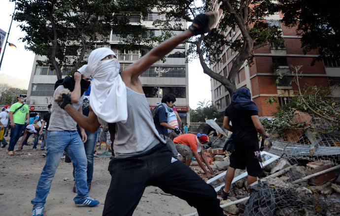 Opposition activists throw stones against National Guard members during a protest against the government of Venezuelan President Nicolas Maduro, in Caracas on March 3, 2014.(AFP Photo /Juan Barreto)