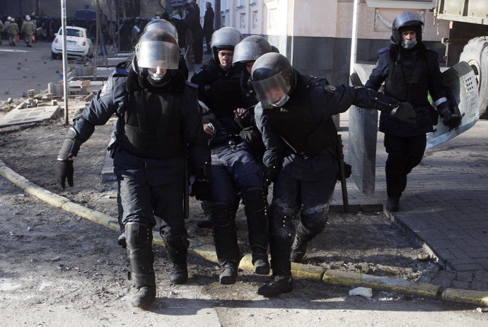 Policemen carry a colleague wounded during clashes with anti-government protesters in Kiev on February 18, 2014. (AFP Photo / Yury Kirnichny)
