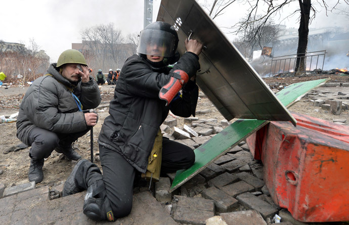 Anti-government protesters take cover as they are under fire reportedly of police sniper during clashes police in the center of Kiev on February 20, 2014.(AFP Photo / Sergei Supinsky)