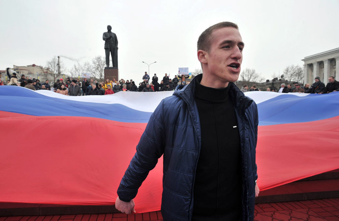 A pro-Russian activist holds part of a giant Russian flag near a statue of Lenin during a rally in Simferopol, the administrative center of Crimea, on March 1, 2014. (AFP Photo)
