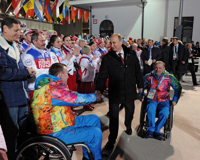 Russian President Vladimir Putin (C) shakes hands with poses with sportsmen as he visits the mountain Paralympic village outside Sochi on March 6, 2014 (AFP Photo)
