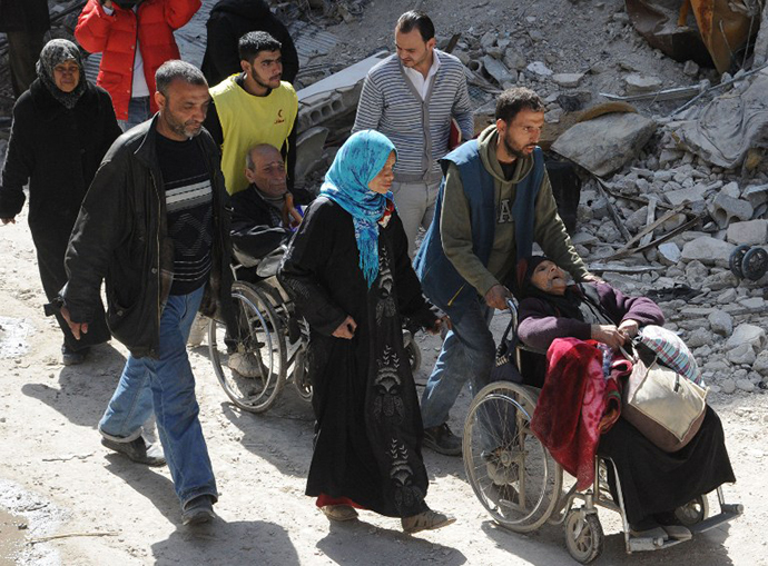 A handout picture released by the official Syrian Arab News Agency (SANA) on February 24, 2014 shows residents of Syria's besieged Yarmuk Palestinian refugee camp, south of Damascus, being evacuated during an operation led by the UN agency for Palestinian refugees UNRWA. (AFP Photo / SANA)