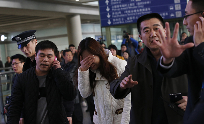 A woman (C), believed to be the relative of a passenger onboard Malaysia Airlines flight MH370, covers her face as she cries at the Beijing Capital International Airport in Beijing March 8, 2014. (Reuters / Kim Kyung Hoon)