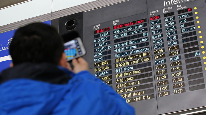 A man takes pictures of a flight information board displaying the Scheduled Time of Arrival (STA) of Malaysia Airlines flight MH370 (top, in red) at the Beijing Capital International Airport in Beijing, March 8, 2014.(Reuters / Kim Kyung-Hoon)