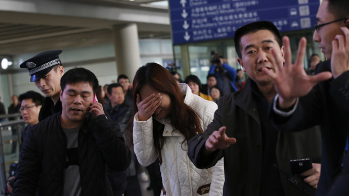 A relative (C, in white) of a passenger onboard Malaysia Airlines flight MH370, covers her face as she cries at the Beijing Capital International Airport in Beijing March 8, 2014.(Reuters / Kim Kyung-Hoon)