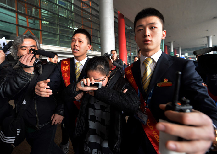 A crying woman is escorted to a bus for relatives at the Beijing Airport after news of the missing Malaysia Airlines Boeing 777-200 plane on March 8, 2014.(AFP Photo / Mark Ralston)