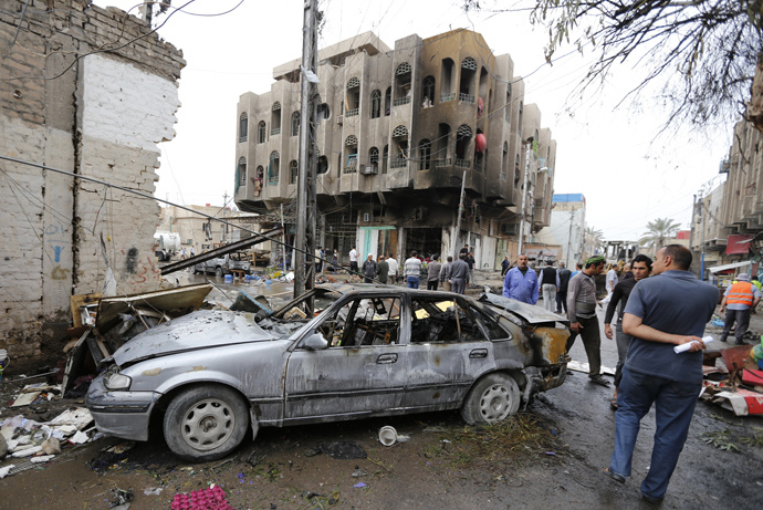 People look at the site of a car bomb attack in the neighbourhood of al-Qahera in northern Baghdad, March 9, 2014 (Reuters / Thaier al-Sudani)