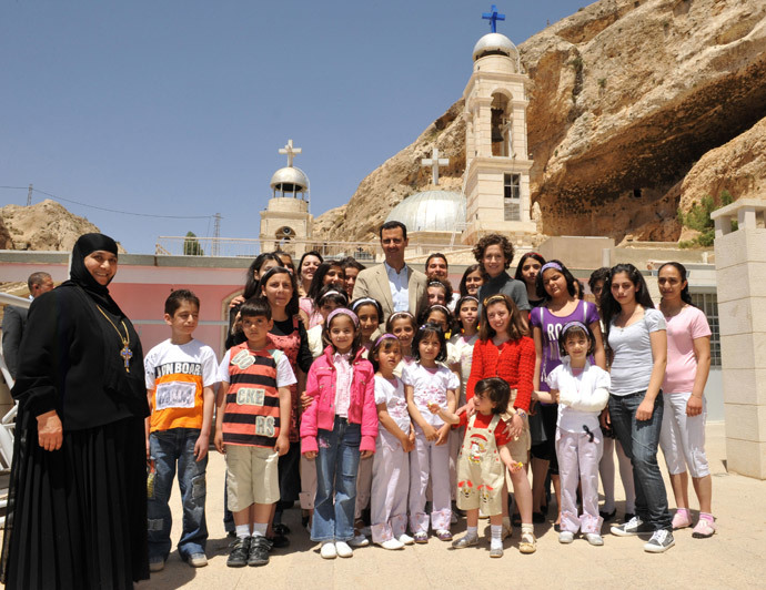 Syrian President Bashar al-Assad and his wife Asma pose for a group photo with orphans at the Mar Taqla convent in Maalula, 60 kms north of Damascus, on April 27, 2008.(AFP Photo / STR)