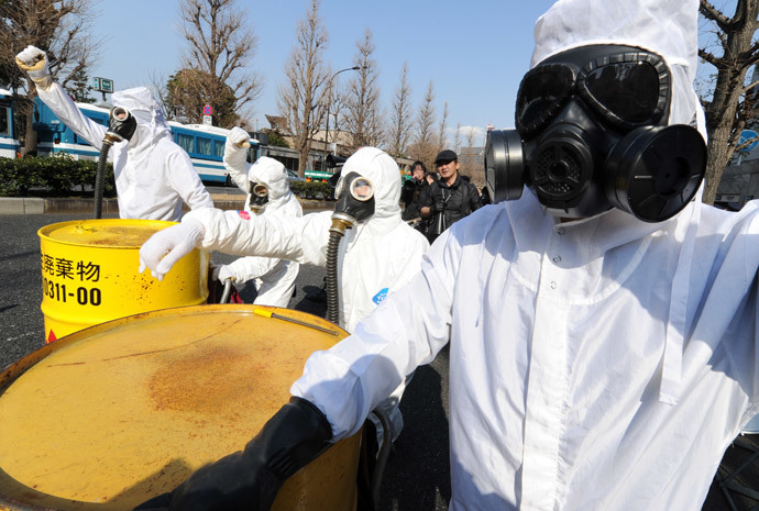 People wearing protective suits and masks shout slogans next to mock drums (L) of nuclear waste from the Fukushima Daiichi nuclear power plant, during a march denouncing nuclear power plants in Tokyo on March 9, 2014. (AFP Photo / Toru Yamanaka)
