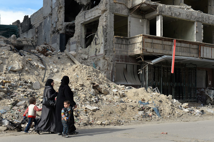 Syrian women walk past the destruction at Dar Al-Shifa hospital in the northern city of Aleppo.(AFP Photo / Miguel Medina)
