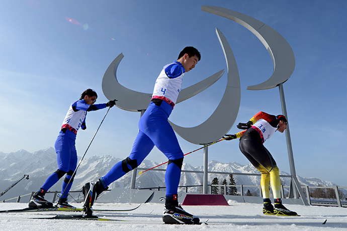 China's Haitao Du (C), China's Dexin Zou (L) and Germany's Tino Uhlig compete during the Men's Cross Country 20 km Classic Standing at XI Paralympic Olympic games in the Rosa Khutor stadium near Sochi on March 10, 2014 (AFP Photo / Kirill Kudryavtsev)