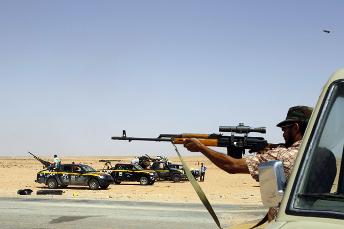 A rebel from Misrata tests his weapon at Bir Doufan check-point about 70 km from Bani Walid (Reuters/Youssef Boudlal)