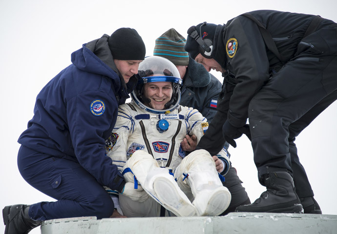 Flight engineer Sergei Ryazansky of Russia is helped out of the Soyuz TMA-10M capsule shortly after the landing in a remote area southeast of the town of Zhezkazgan in central Kazakhstan, March 11, 2014. (Reuters / Bill Ingalls / NASA / Handout via Reuters)