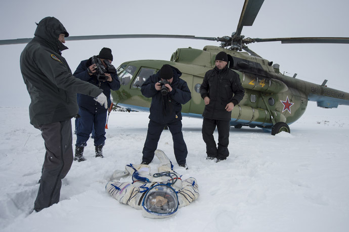 A photographer and an operator document the suit worn byAstronaut Michael Hopkins from NASA after the landing of the Soyuz TMA-10M capsule in a remote area southeast of the town of Zhezkazgan in central Kazakhstan, March 11, 2014. (Reuters / Bill Ingalls / NASA / Handout via Reuters)