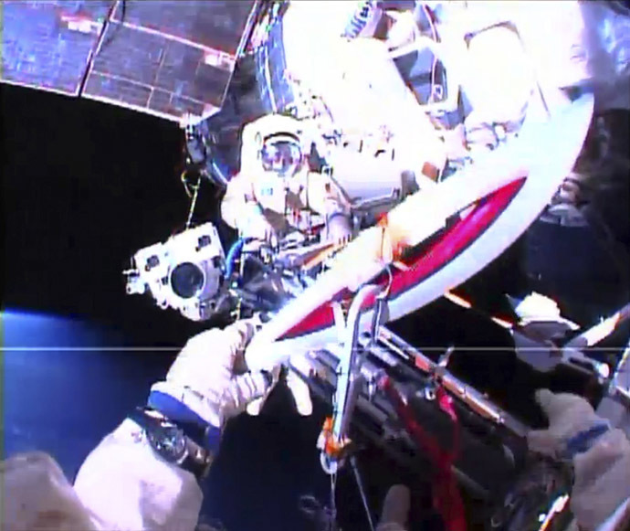 Russian astronaut Oleg Kotov holds an Olympic torch as he takes it on a spacewalk as Russian astronaut Sergei Ryazansky prepares the camera outside the International Space Station in this still image taken from video courtesy of NASA TV, November 9, 2013. (Reuters/NASA)