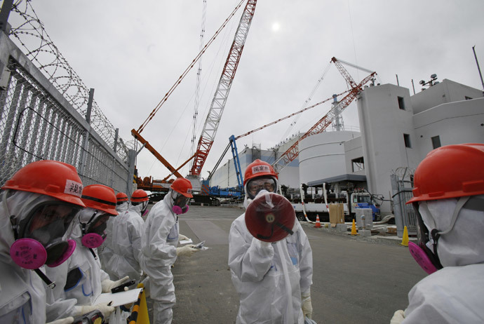 An employee (C) of Tokyo Electric Power Co. (TEPCO), wearing a protective suit and a mask, gives an explanation in front of No. 1 reactor building at the Tokyo Electric Power Co's (TEPCO) tsunami-crippled Fukushima Daiichi nuclear power plant in Fukushima prefecture March 10, 2014. (Reuters / Koji Sasahara / Pool)