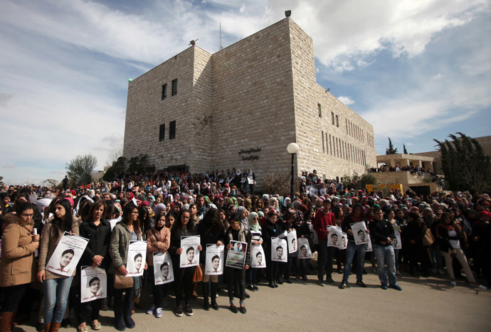 Palestinian students from the Bir zeit University attend the funeral procession of their comrade Saji Sayel Darwish (portraits) who was killed the previous day by Israeli soldiers, on March 11, 2014 in the northern West Bank town of Bir Zeit. (AFP Photo/Abbas Momani)