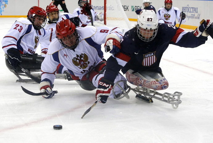 Joshua Pauls of the U.S. (R) fights for the puck with Russia's Konstantin Shikhov (C) and Ilia Volkov during their ice sledge hockey game at the 2014 Sochi Paralympic Winter Games, March 11, 2014. (Reuters / Alexander Demianchuk)