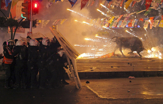 Riot policemen shield themselves as fireworks thrown by protesters explode next to the statue of a bull, during an anti-government protest in the Kadikoy district of Istanbul March 11, 2014. (Reuters)