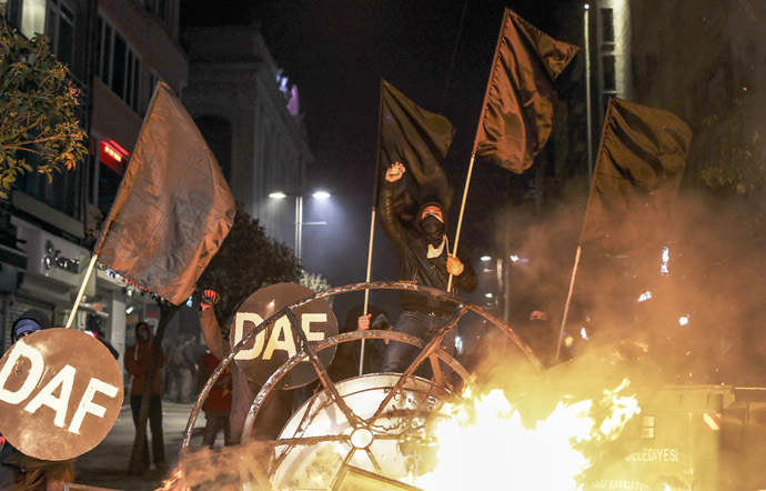 Protesters chant slogans behind a barricade during clashes with riot police in Kadikoy, on the Anatolian side of Istanbul, on March 11, 2014. (Reuters)