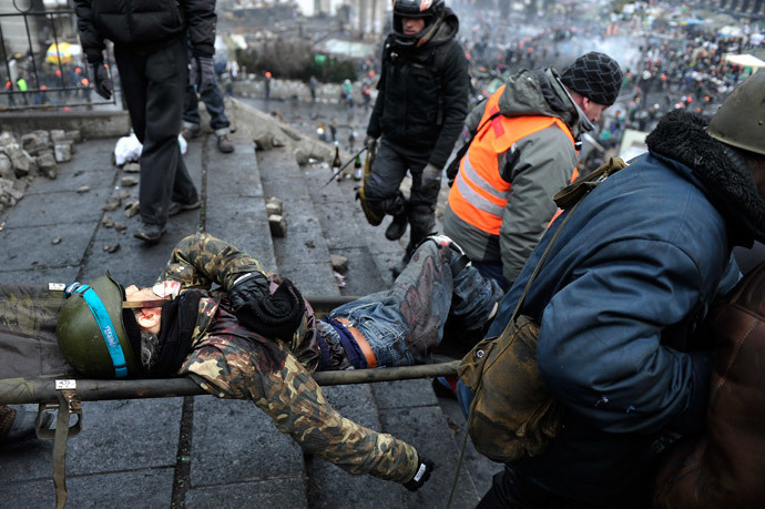 Protesters evacuate a wounded demonstrator from Independence square, dubbed Maidan, in Kiev on February 20, 2014. (AFP Photo / Louisa Gouliamaki)