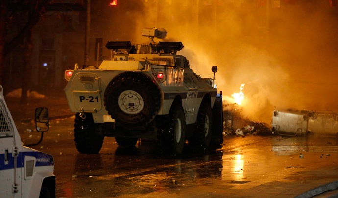 An armoured police vehicle drives through a barricade on fire during a demonstration in Ankara March 12, 2014. (Reuters / Umit Bektas)