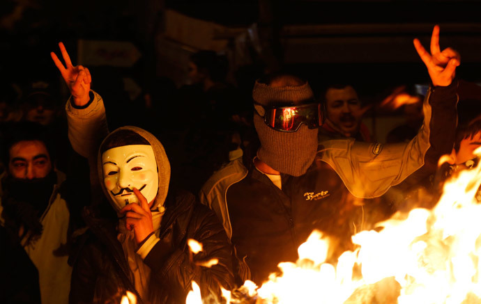 An anti-government protester wearing a Guy Fawkes mask stands with others behind a barricade that they set on fire during a demonstration in Ankara March 12, 2014. (Reuters / Umit Bektas)