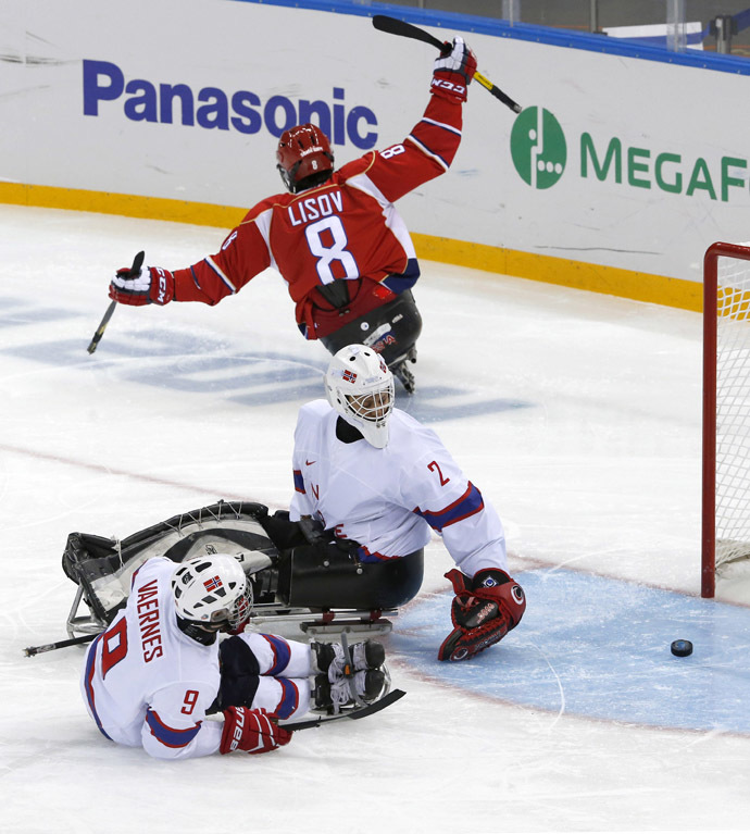 Russia's Dmitrii Lisov scores against Norway's Morten Vaernes (L) and Kristian Buen (C) during the semi-final sledge hockey game at the 2014 Sochi Winter Paralympic Games March 13, 2014. (Reuters)