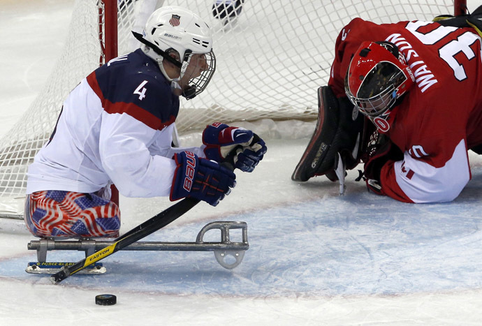 Brody Roybal of the U.S celebrates a goal against Canada's Corbin Watson (R) during the semi-final sledge hockey game at the 2014 Sochi Winter Paralympic Games March 13, 2014. (Reuters)