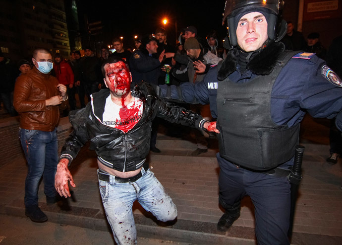 A police officer escorts a wounded participant of an anti-war rally during clashes with pro-Russian demonstrators in Donetsk March 13, 2014. (Reuters / Stringer)